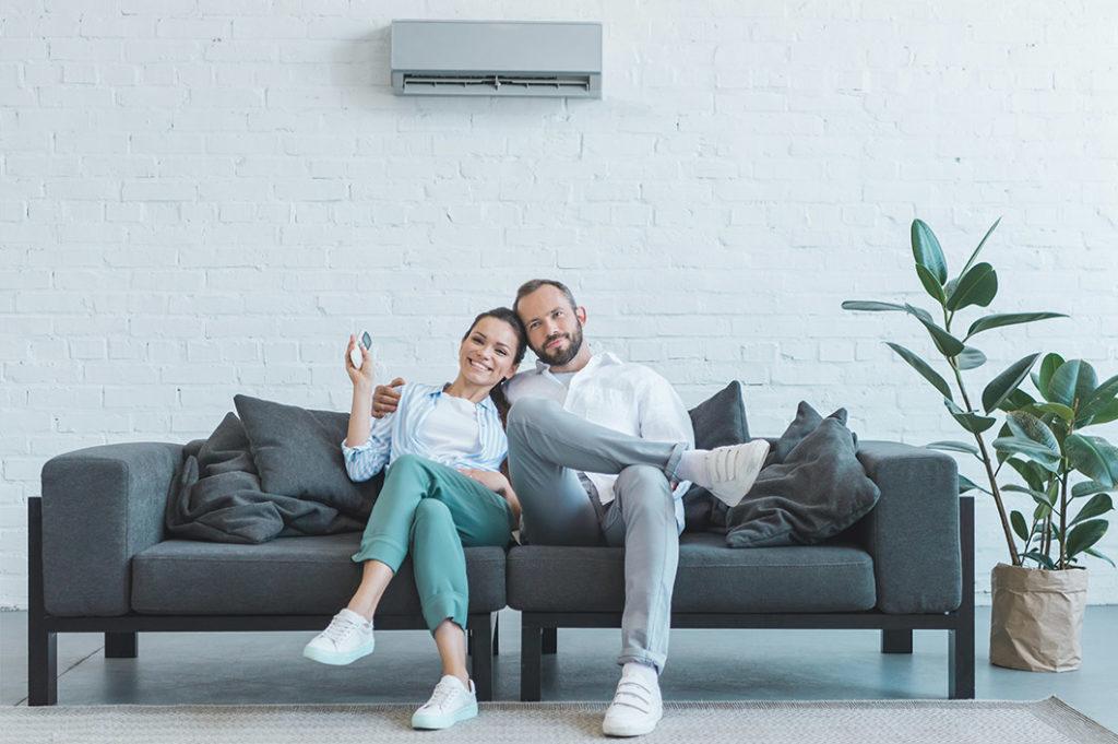 Pärchen sitzt auf dem Sofa und die Frau hat die Fernbedienung in der hand. Hinten ist an der Wand die Klimanlage