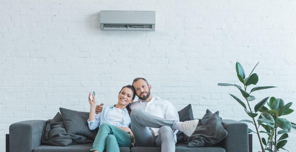 ein Pärchen sitz glücklich auf dem Sofa vor Ihrer Klimaanlage