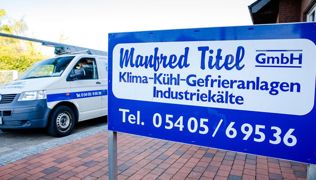 Firmenschild von Manfred Titel mit dem Firmenbulli im Hintergrund